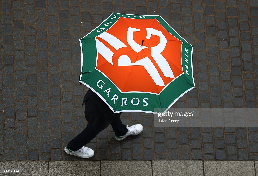 A spectator shelters under an umbrella as rain stops play on day one of the 2016 French Open at Roland Garros on May 22, 2016 in Paris, France.