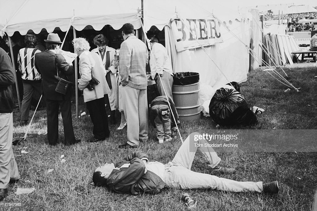 A spectator sprawls beside the beer tent during the Epsom Derby in Surrey, 8th June 1989.
