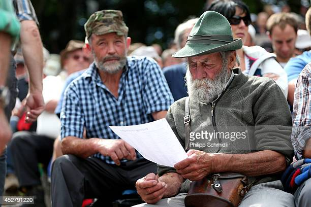 A spectator studies the ranking between the fights during the Alpine Wrestling Festival BruenigSchwinget at the top of the Bruenig Pass on July 27...