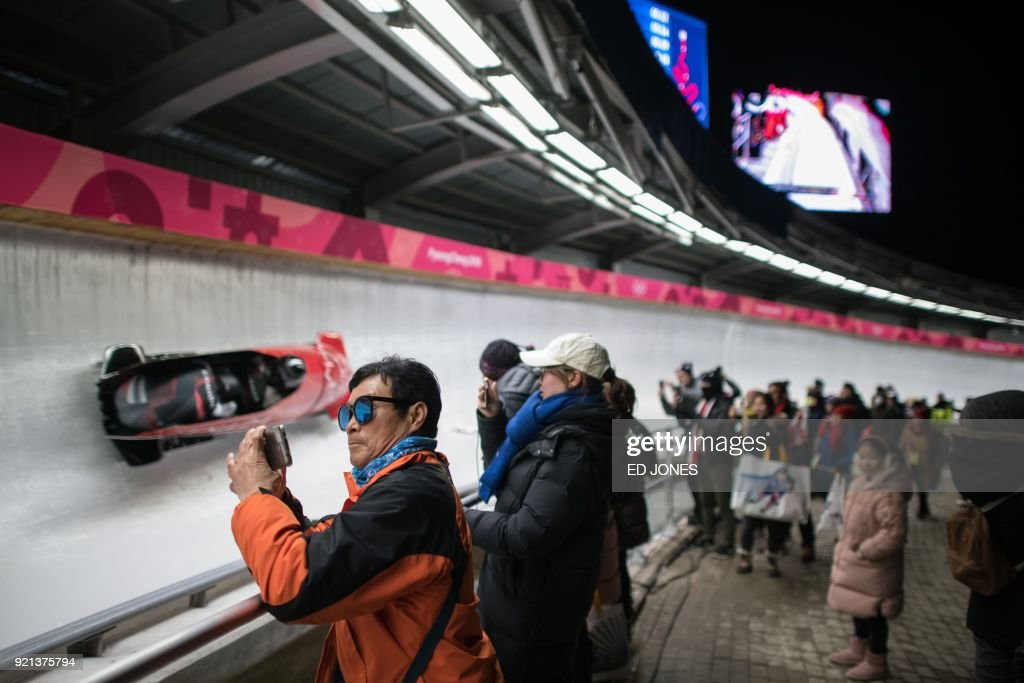 TOPSHOT - A spectator takes a photo beside the track during the women's bobsleigh heats during the Pyeongchang 2018 Winter Olympic Games at the Olympic Sliding Centre in Pyeongchang on February 20, 2018. / AFP PHOTO / Ed JONES