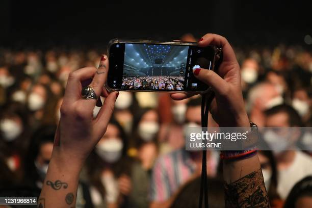 Spectator takes a picture before the start of a rock music concert by Spanish group Love of Lesbian at the Palau Sant Jordi in Barcelona on March 27,...