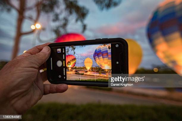 Spectator takes cell phone photo of tethered hot air balloons illuminated by their burners at the Hot Air Halloween Balloon Glow on October 31, 2020...