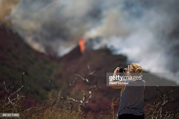 A spectator takes photos at the Blue Cut Fire on August 18 2016 near Wrightwood California An unknown number of homes and businesses have burned and...