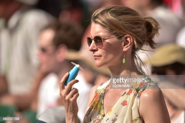 A spectator uses a fan as she watches Switzerland's Roger Federer play against Britain's Andy Murray in their men's semifinal match on day eleven of...