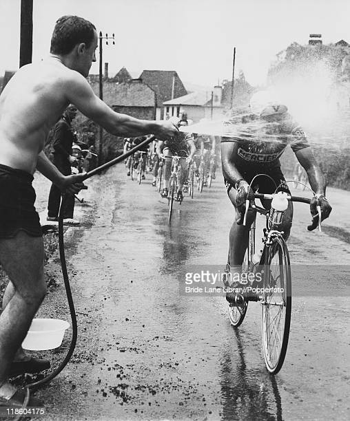 A spectator uses a hosepipe to cool off French cyclist JeanPierre Genet during the 11th stage of the Tour de France between Bayonne and Pau 9th July...