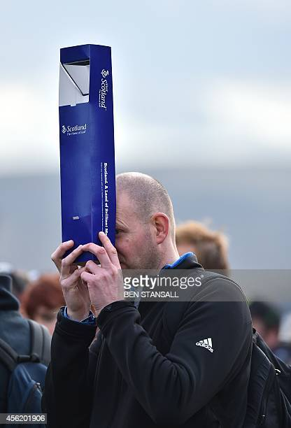 A spectator uses a periscope to watch play during Saturday's foursomes matches on the second day of the Ryder Cup golf tournament at the Gleneagles...