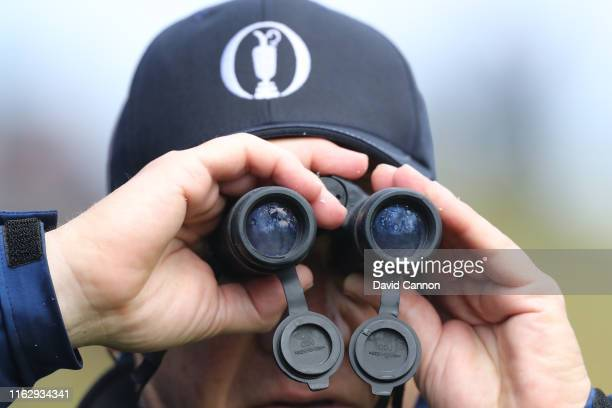 A spectator using binoculars to watch the play during the first round of the 148th Open Championship held on the Dunluce Links at Royal Portrush Golf...