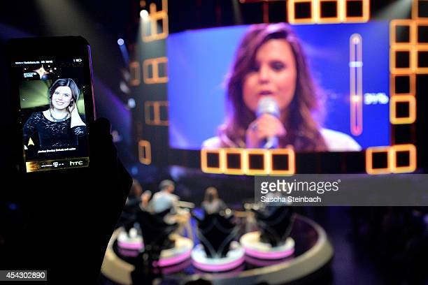 A spectator votes via smartphone app for Janine Densie Schulz during the first live show of 'Rising Star' at Coloneum on August 28 2014 in Cologne...