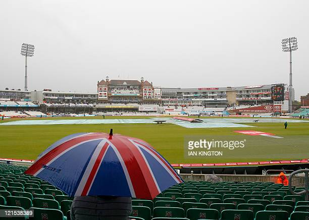 Spectator waits under an umbrella as rain delays play after the lunch interval during day 3 of the fourth Test match between England and India at The...
