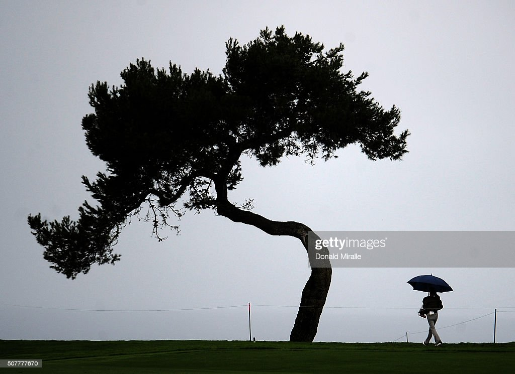 A spectator walks off the course as wind and rain delay play during the final round of the Farmers Insurance Open at Torrey Pines South on January 31, 2016 in San Diego, California.