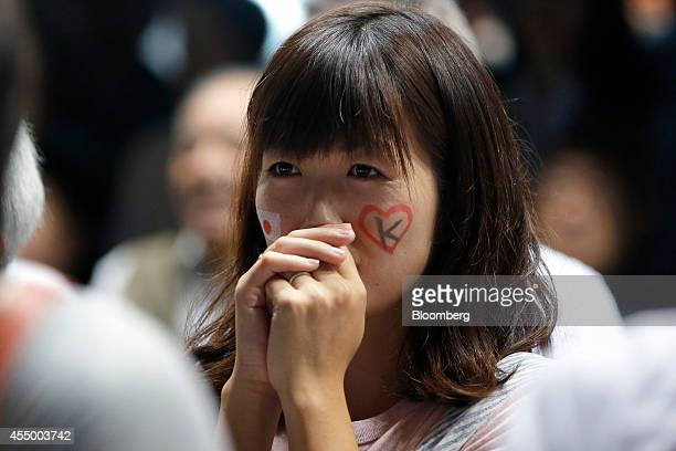 A spectator watches as Japan's Kei Nishikori plays against Croatia's Marin Cilic in the US Open Tennis Championships men's singles final match at a...