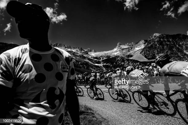 A spectator watches as riders of a breakaway group Spain's Mikel Nieve Netherlands' Marco Minnaard and Colombia's Daniel Martinez ride up the Col de...