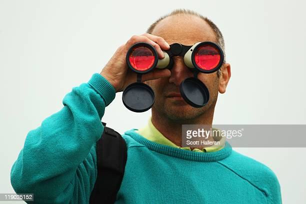 Spectator watches the action through a pair of binoculars during the first round of The 140th Open Championship at Royal St George's on July 14, 2011...