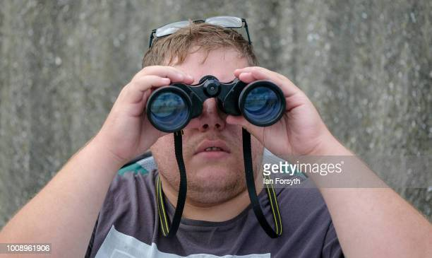 A spectator watches the display through binoculars during the 30th Sunderland International Air show on July 28 2018 in Sunderland England Held over...