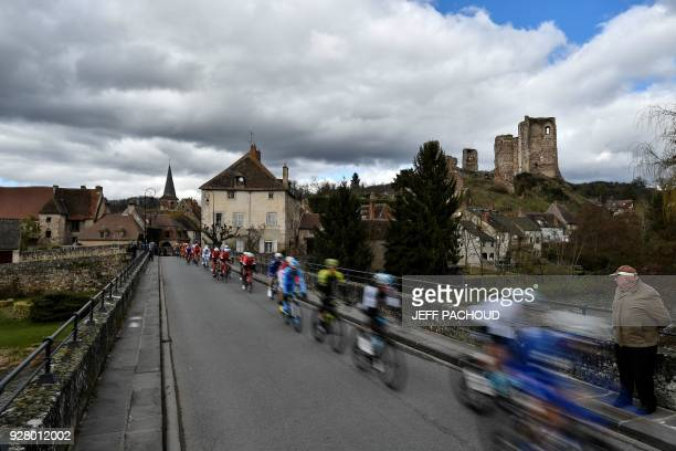A spectator watches the pack riding past the 11th Century fortified castle Chateau d'Herisson during the third stage of the Paris Nice cycling race...