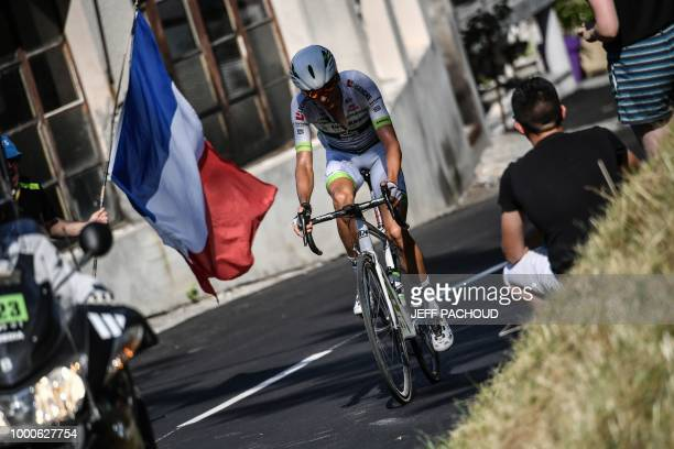 A spectator waves a French flag as France's Warren Barguil rides a counter attack during the tenth stage of the 105th edition of the Tour de France...