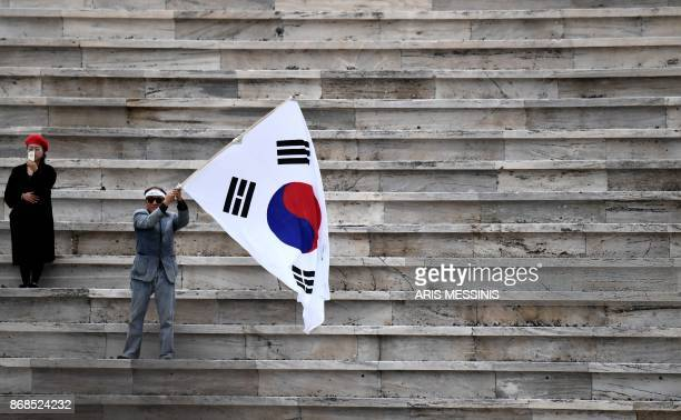 A spectator waves a South Korean flag as another uses a cellular telephone at The Panathenaic Stadium in Athens on October 31 during the handover...