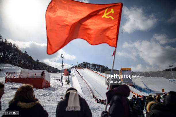 A spectator waves a Soviet flag during the Men's Halfpipe Qualification Run 1 snowboarding competition at Phoenix Park on day four of the PyeongChang...