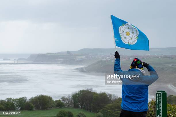 A spectator waves a Yorkshire flag as he waits for riders on Cote Lythe Bank during Stage 2 of the Women's race of the Tour de Yorkshire cycling race...