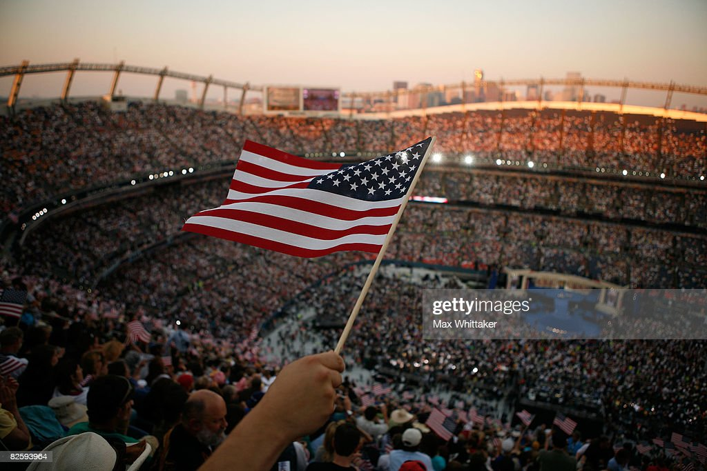 A spectator waves American flags on day four of the Democratic National Convention (DNC) at Invesco Field at Mile High August 28, 2008 in Denver, Colorado. U.S. Sen. Barack Obama (D-IL) is the first African-American to be officially nominated as a candidate for U.S. president by a major party.