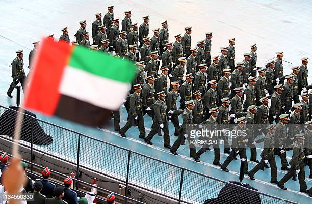 A spectator waves the Emirati flag as troops march during celebrations marking the 40th anniversary of the establishment of the United Arab Emirates...