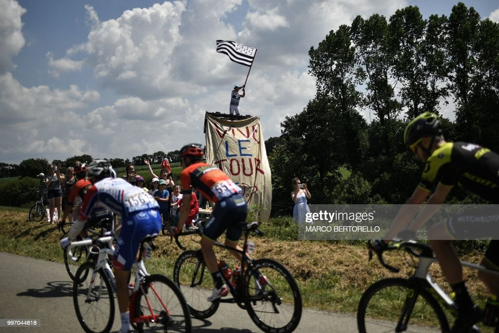 TOPSHOT - A spectator waves the flag of Brittany during the sixth stage of the 105th edition of the Tour de France cycling race between Brest and Mur-de-Bretagne Guerledan, western France, on July 12, 2018.