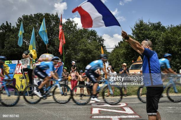 A spectator waves the French flag as riders of Spain's Movistar Team cycling team cycle past during the fourth stage of the 105th edition of the Tour...