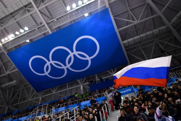 A spectator waves the Russia flag during the men's preliminary round ice hockey match between the Olympic Athletes from Russia and Slovenia during...