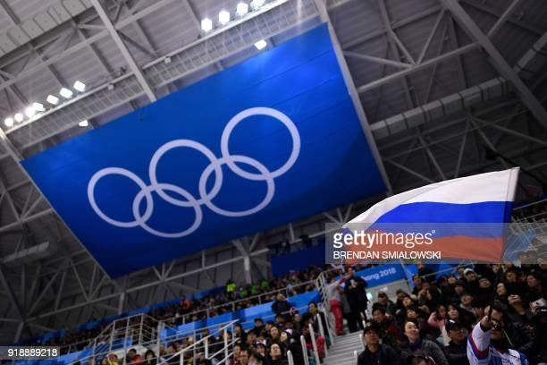 Spectator waves the Russia flag during the men's preliminary round ice hockey match between the Olympic Athletes from Russia and Slovenia during the...