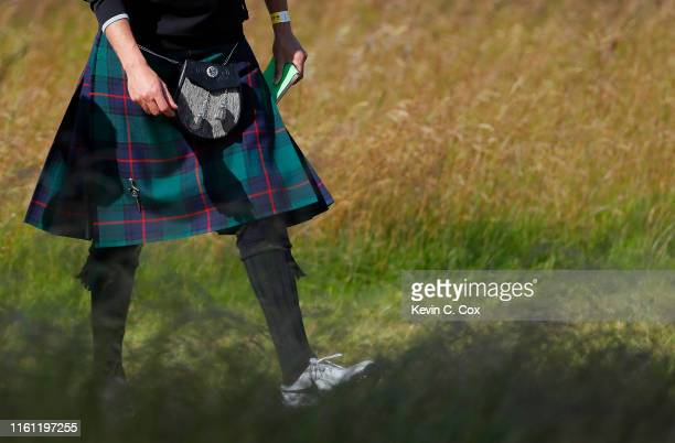 A spectator wearing a kilt walks the first hole during the proam event prior to the start of the Aberdeen Standard Investments Scottish Open at The...