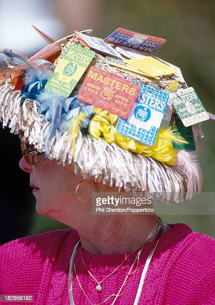 A spectator wearing a straw hat festooned with past Masters entry tickets watching the US Masters Golf Tournament held at the Augusta National Golf...