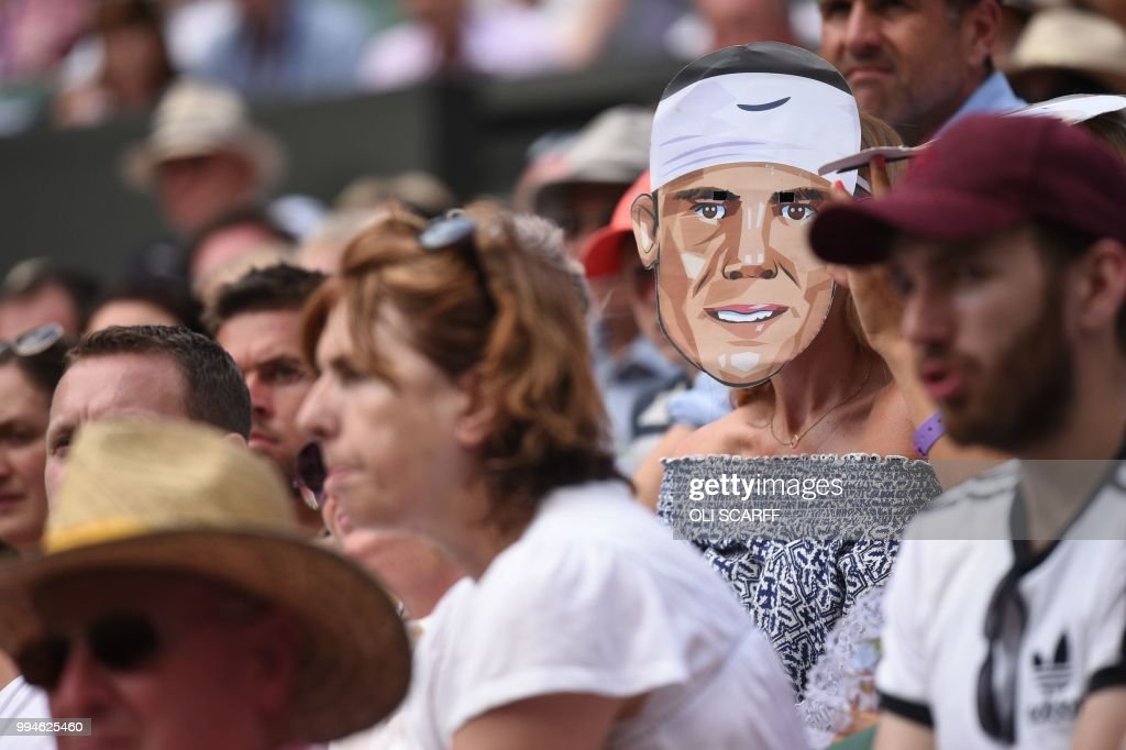TOPSHOT - A spectator wears a mask of Spain's Rafael Nadal as he plays Czech Repbulic's Jiri Vesely in their men's singles fourth round match on the seventh day of the 2018 Wimbledon Championships at The All England Lawn Tennis Club in Wimbledon, southwest London, on July 9, 2018. (Photo by Oli SCARFF / AFP) / RESTRICTED