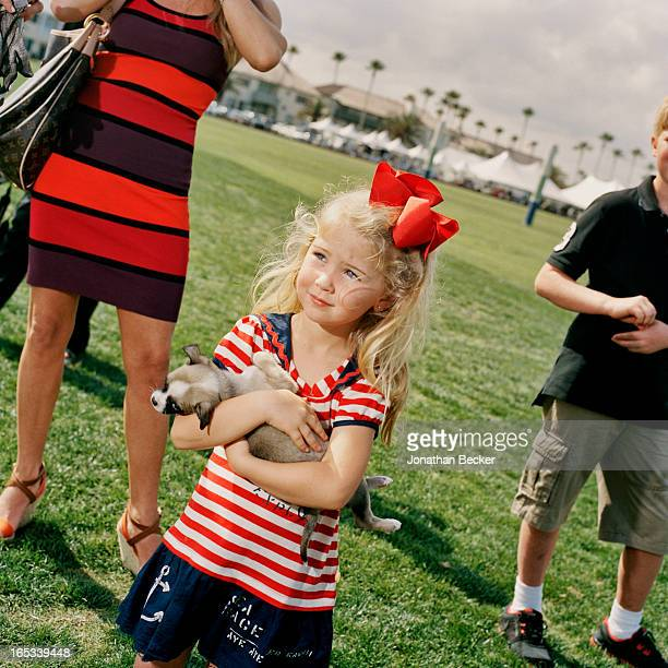 A spectator with puppy is photographed for Town Country Magazine during the first Windsor Charity Polo Cup on February 18 2012 in Vero Beach Florida...