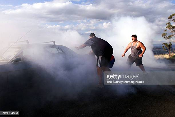 Spectators amuse themselves on the hill at Mount Panorama as Bill Ellman does a burnout in his $500 Ford Fairlane with some assistance from his mates...