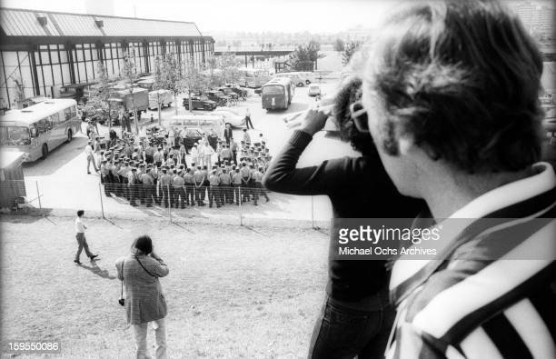 Spectators and cameramen watch as West German Police gather near the quarters of the Israili Olympic team where members of the Black September...