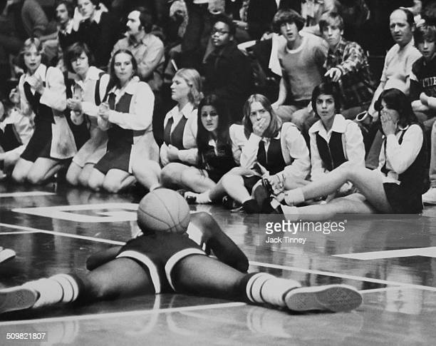 Spectators and cheerleaders near courtside react in distress as an unidentified basketball player with a ball on his back lies prone on the court 1970