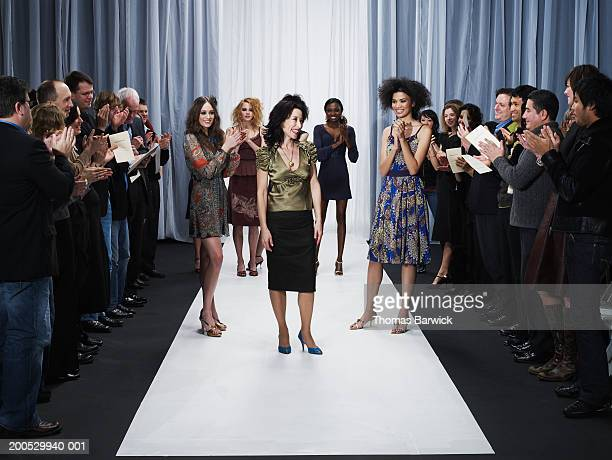 spectators and models applauding for designer on catwalk - modeshow stockfoto's en -beelden