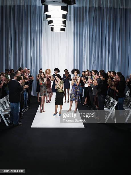 spectators and models applauding for designer on catwalk - catwalk stage stock pictures, royalty-free photos & images