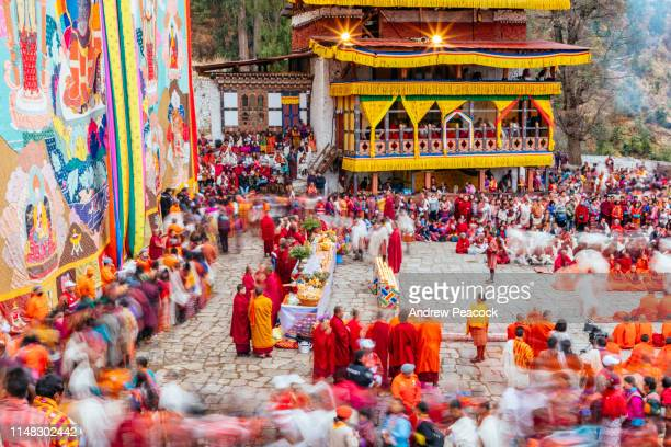 spectators and monks in colorful clothing at the paro festival - paro stock pictures, royalty-free photos & images