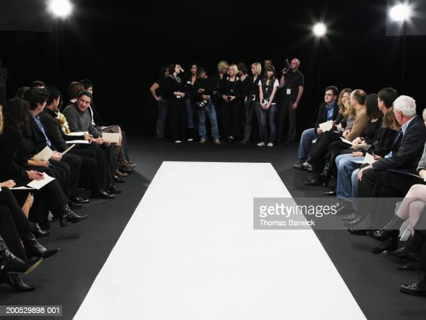 spectators and photographers surrounding catwalk at fashion show - fashion runway stock pictures, royalty-free photos & images