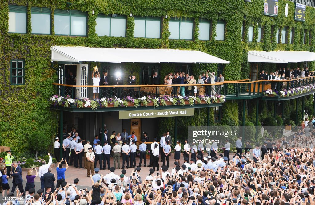 Spectators applaud and take photographs as Roger Federer of Switzerland celebrates victory with the trophy on the balcony after the Gentlemen's Singles final against Marin Cilic of Croatia on day thirteen of the Wimbledon Lawn Tennis Championships at the All England Lawn Tennis and Croquet Club at Wimbledon on July 16, 2017 in London, England.