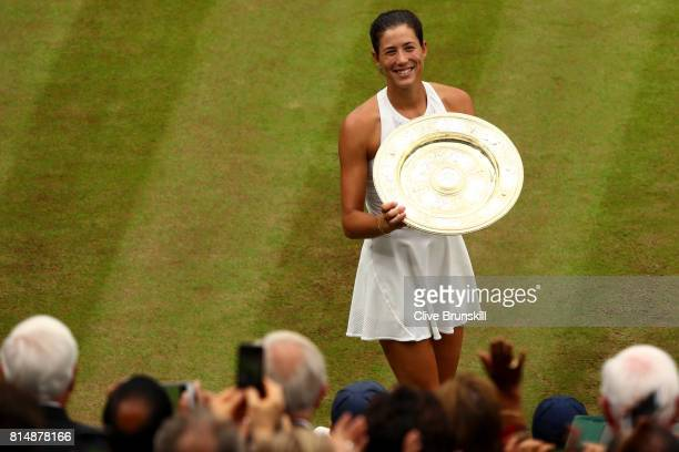 Spectators applaud as Garbine Muguruza of Spain celebrates victory with the trophy after the Ladies Singles final against Venus Williams of The...