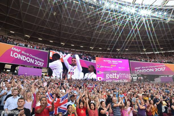Spectators applaud during the medal ceremony for gold medallists Britain's Chijindu Ujah Adam Gemili Daniel Talbot and Nethaneel MitchellBlake for...