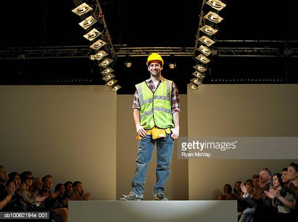 spectators applauding construction worker on catwalk - catwalk stage stock pictures, royalty-free photos & images