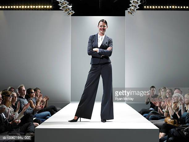 spectators applauding female fashion designer on catwalk - catwalk stock photos and pictures