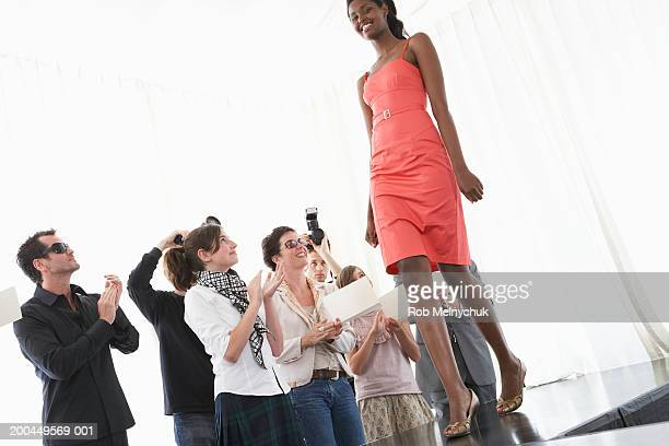 Spectators applauding female model on runway during fashion show
