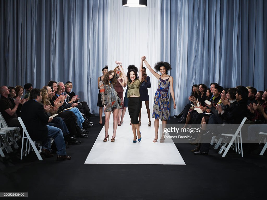 Spectators applauding for designer and female models on catwalk : Stock Photo