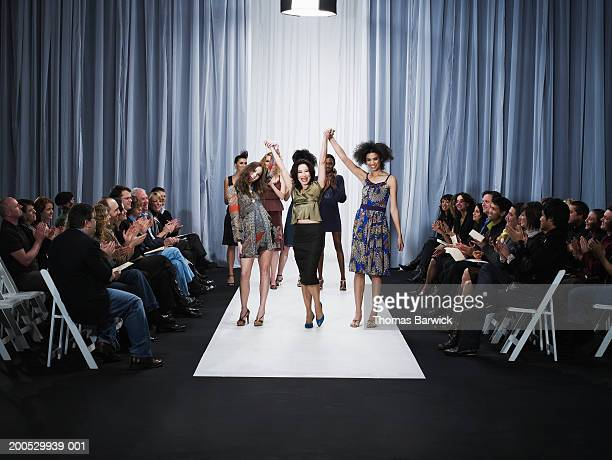spectators applauding for designer and female models on catwalk - sfilata di moda foto e immagini stock
