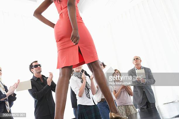 Spectators applauding for female model on runway at fashion show