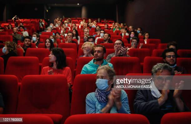 Spectators applauds before the screening of the film Les Parfums on June 21 2020 in Paris following the reopening of movie theaters with the easing...